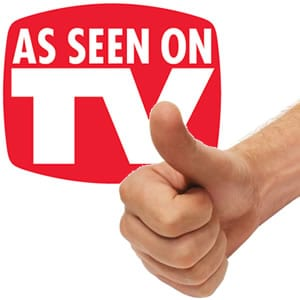 'As Seen on TV' sign behind a hand doing the thumb's up